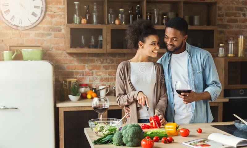 Älska afrikanska amerikanen koppla ihop att förbereda sallad och att dricka rött vin arkivbild