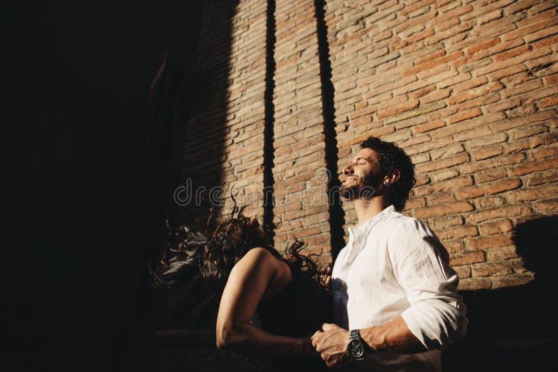 Älska att tycka om för par gå i staden Bak dem är bakgrunden är en vägg för röd tegelsten royaltyfri foto
