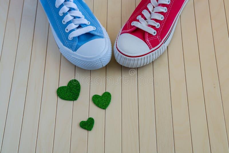 Älska bakgrund med olika gymnastikskor och göra grön hjärtor royaltyfria foton