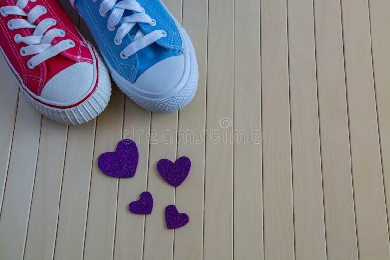 Älska bakgrund med olika gymnastikskor och purpurfärgade hjärtor royaltyfri foto