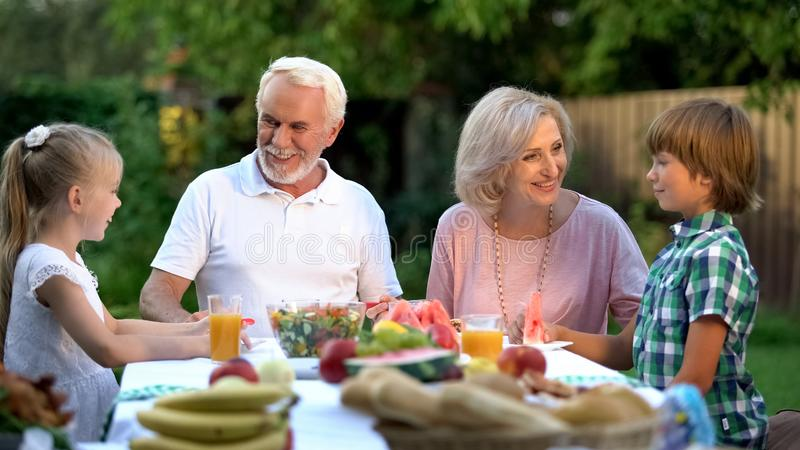 Älska barnbarn som besöker morföräldrar, lyckliga höga par som beundrar ungar arkivfoto