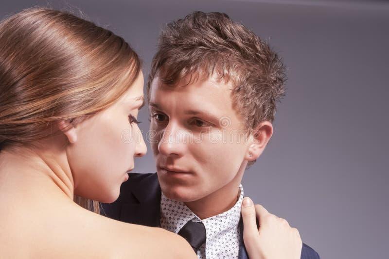 Älska Caucasian par som tillsammans poserar Mot gr? f?rger royaltyfria foton