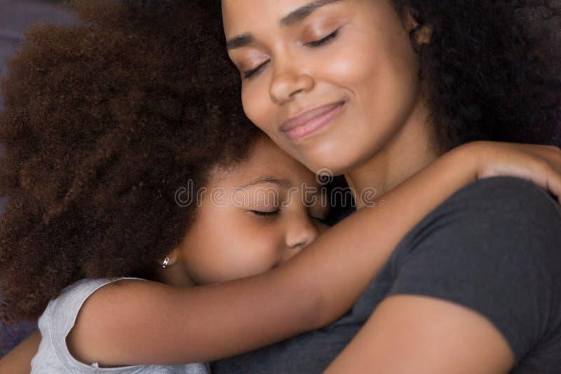 Älska den enkla svarta modern kramar gullig anslutning för dotterkänselmjukhet royaltyfri bild