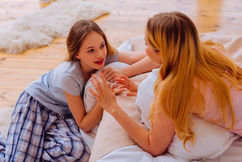 Älska denhaired systern som talar till hennes gulliga blåögda sibling royaltyfria foton