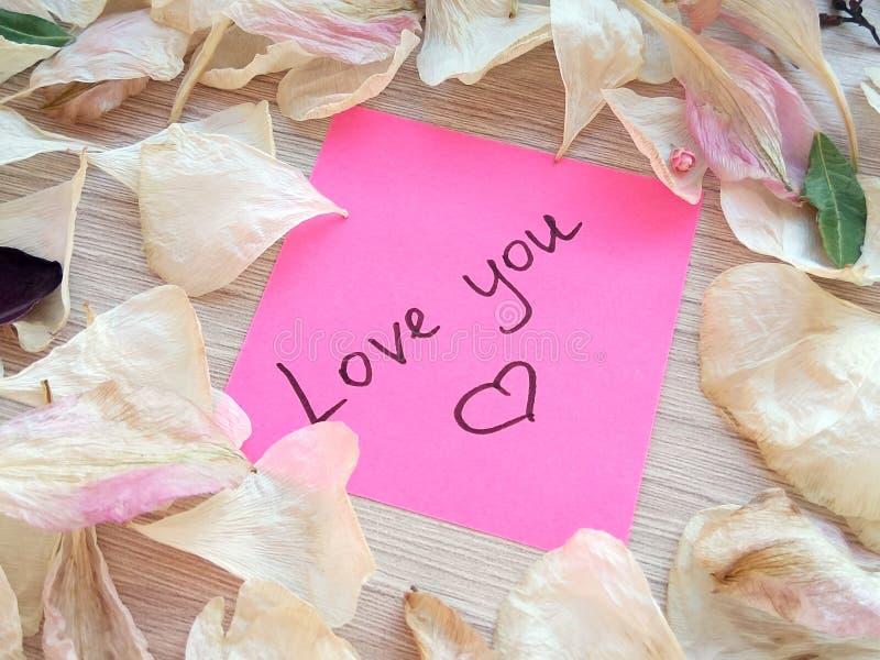 Älska dig meddelandet på rosa klibbig anmärkning med torra ros- och orkidéblommakronblad på trätabellbakgrund royaltyfri bild