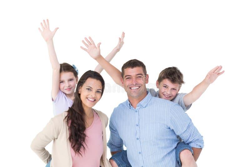 Älska föräldrar som på ryggen ger ritt till barn royaltyfria bilder