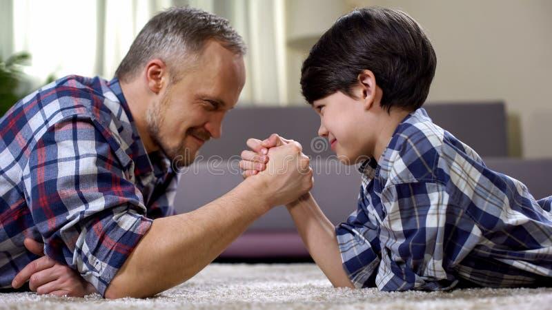 Älska fader- och ungearmbrottning på golvet, helgfritid hemma, gyckel royaltyfri fotografi
