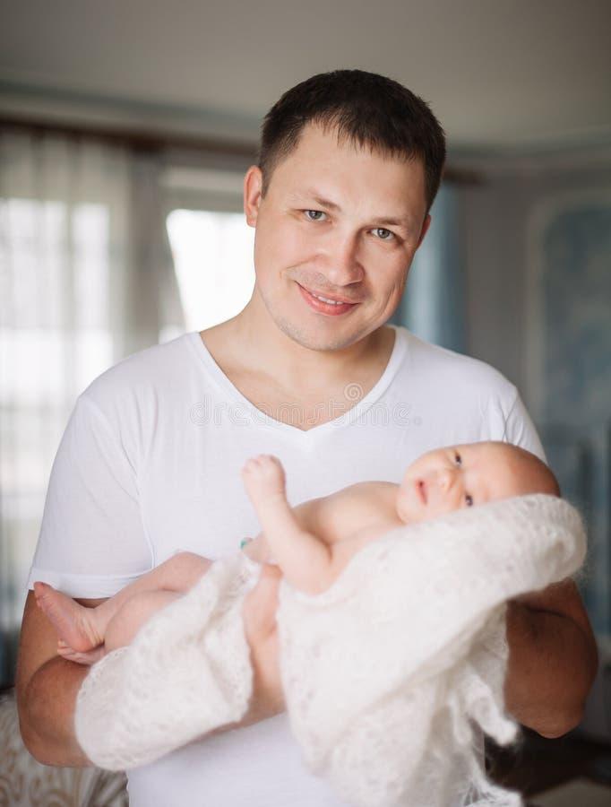 Älska fadern kysser hans nätta nyfödda dotter royaltyfria foton