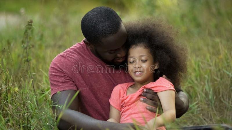 Älska fadern som kramar ömt hans mycket lilla dotter som tillsammans spenderar utomhus- tid royaltyfria foton