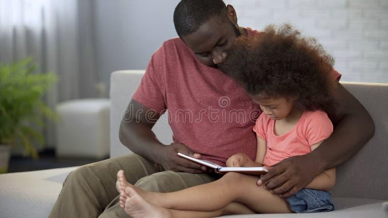 Älska fadern som undervisar hans lilla lockig-haired dotter hur man läser, omsorg royaltyfria bilder