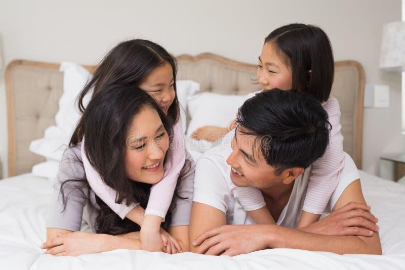 Älska familjen av fyra som hemma ligger i säng arkivbilder