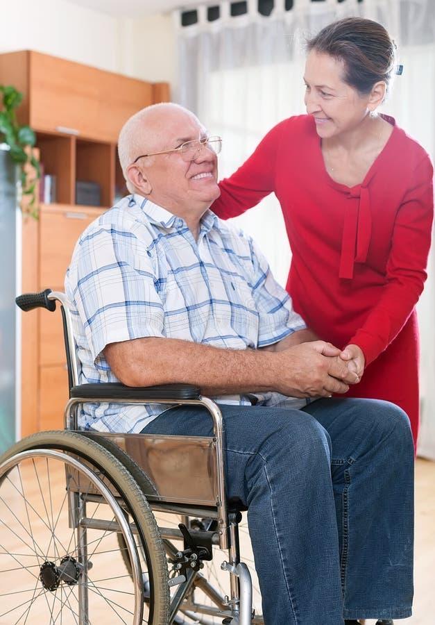 Älska frun bredvid hennes make i rullstol arkivfoto