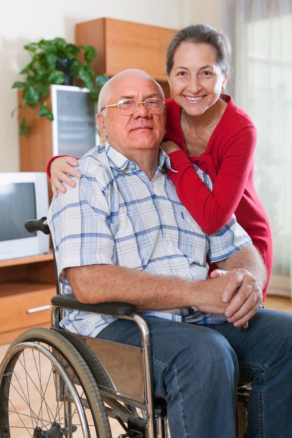 Älska frun bredvid make i rullstol royaltyfria bilder