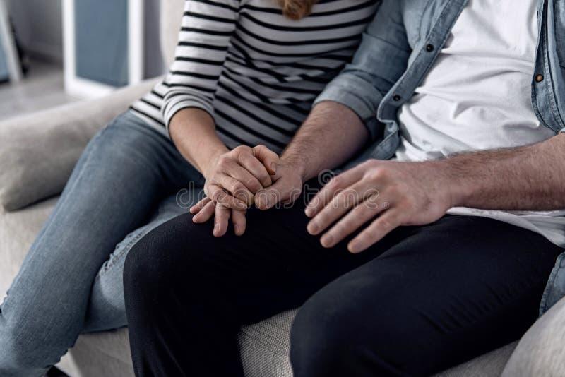 Älska frun som rymmer en hand av hennes make, medan sitta med honom royaltyfria foton