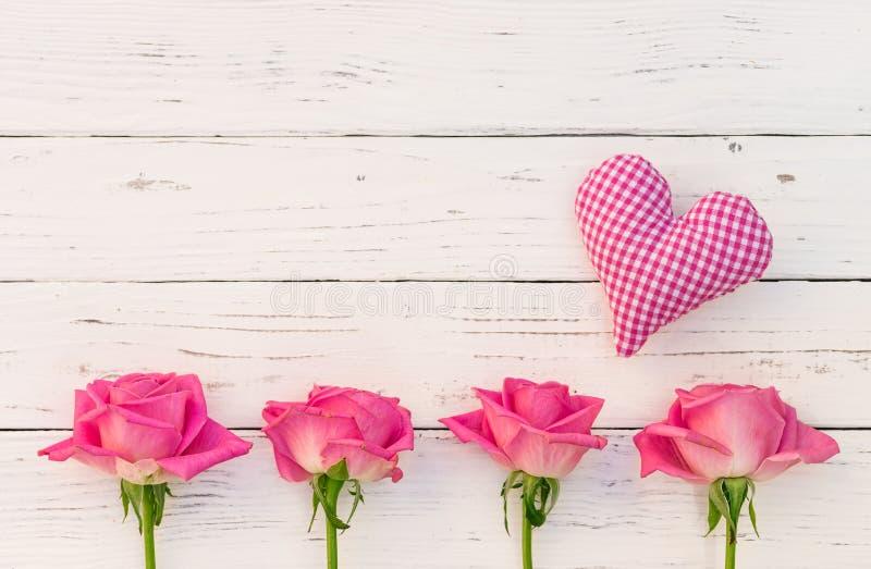 Älska hälsningkortet med rosa hjärta och rosor på vit wood bakgrund royaltyfri foto