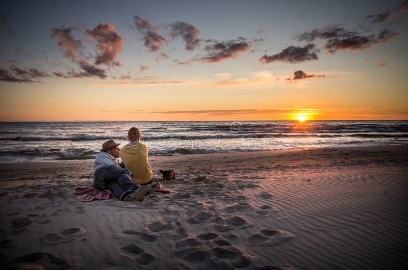 Älska hållande ögonen på solnedgång för par arkivbild