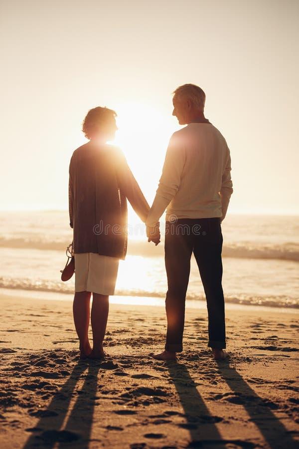 Älska höga par som kopplar av vid havet arkivfoto