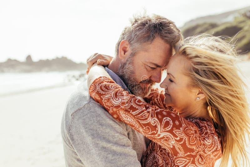 Älska höga par som omfamnar på stranden royaltyfria bilder