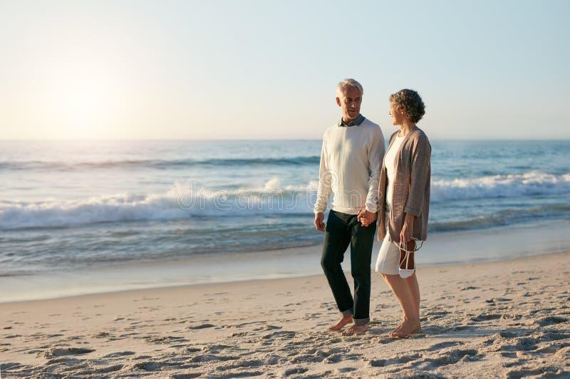Älska höga par som promenerar stranden i afton royaltyfria foton
