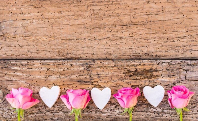 Älska hjärtor, och rosa rosblommor gränsar på lantligt trä, förälskelsebakgrund för att gifta sig eller valentindag arkivfoto