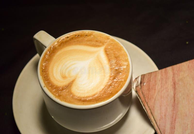 Älska kaffe, a-kopp av lattekonst med hjärtamodellen i en vit kopp inomhus kafé royaltyfria bilder