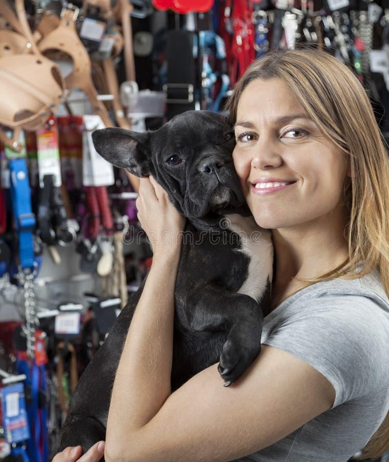 Älska kvinnan som omfamnar den franska bulldoggen i lager royaltyfri bild
