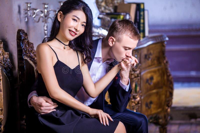 Älska kyssande lyckliga kvinnas för man hand, medan sitta på stol hemma royaltyfria foton