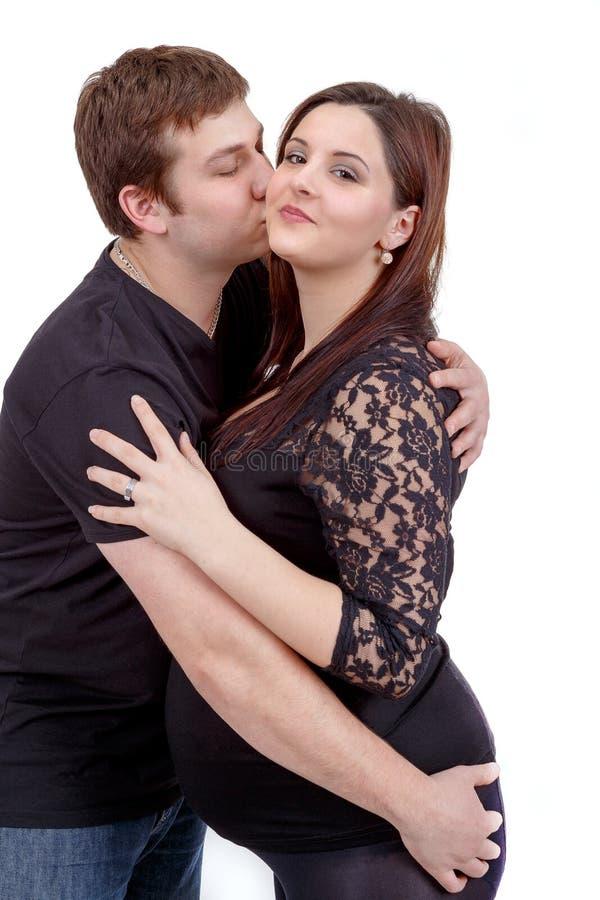 Älska lyckliga par, kyssande gravid kvinna för make royaltyfri bild