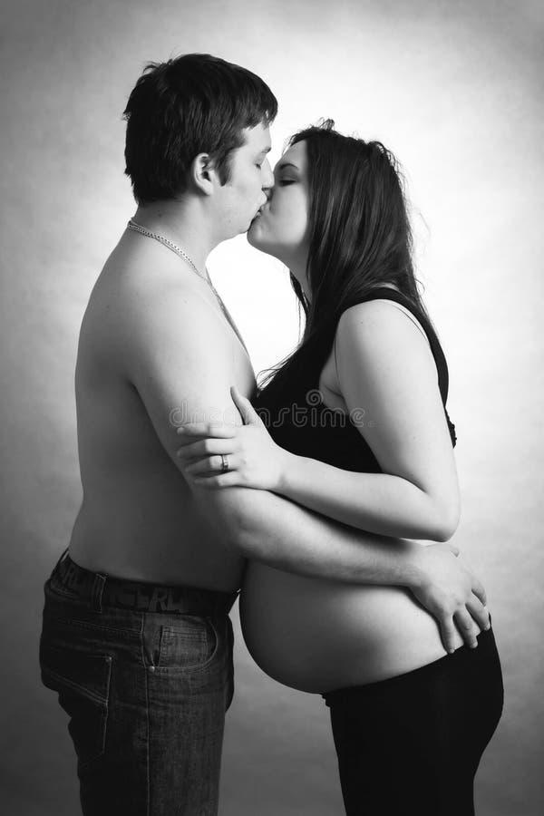 Älska lyckliga par, kyssande gravid kvinna för make arkivfoton