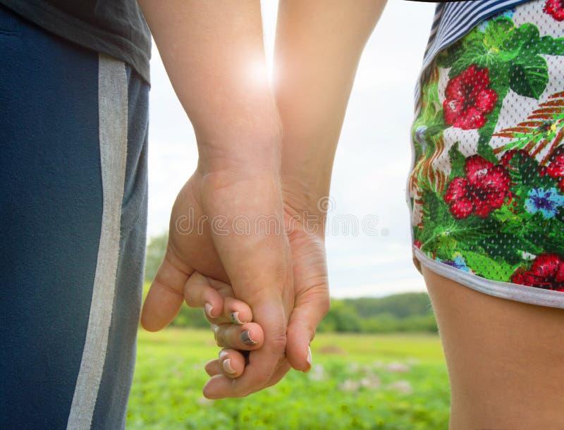 Älska mannen och kvinnan som rymmer händer, solljussken till och med deras händer fotografering för bildbyråer