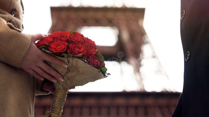 Älska mannen som ger den härliga buketten av scharlakansröda rosor till hans älskling, förälskelse royaltyfria foton