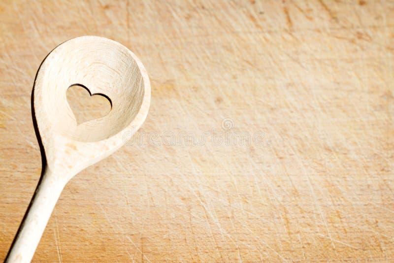 Älska matlagningbakgrundsbegreppet med den gamla retro skeden med hjärtatecknet royaltyfria foton