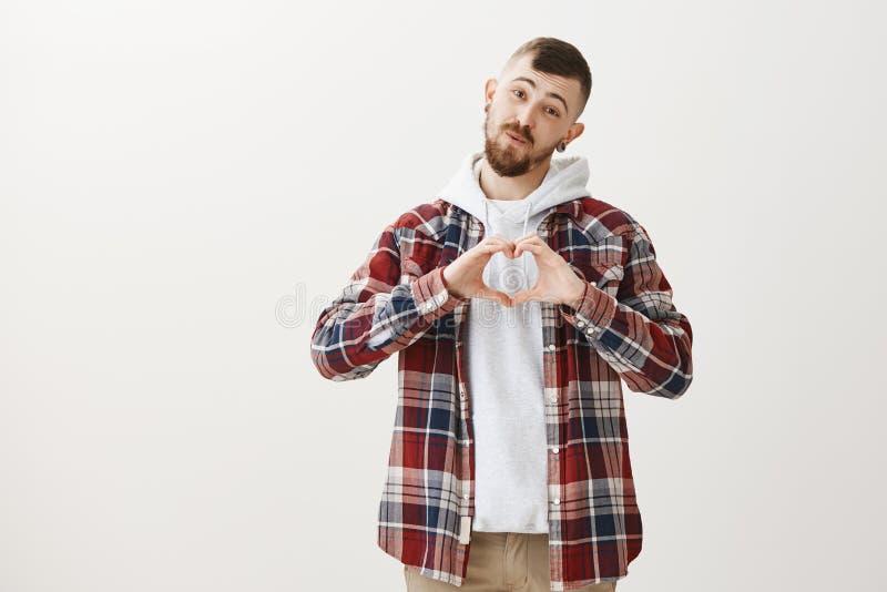 älska mig som är mjuk Gullig vänlig bästa vän i stilfull gatastilkläder och att visa hjärtagest över bröstkorg och vikning fotografering för bildbyråer
