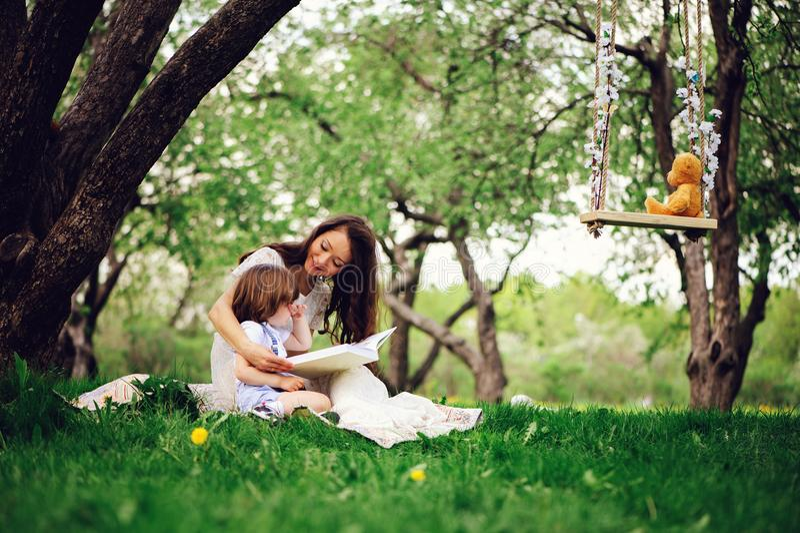 älska moderläseboken till litet barnsonen som är utomhus- på picknick i vår eller sommar, parkera royaltyfri bild