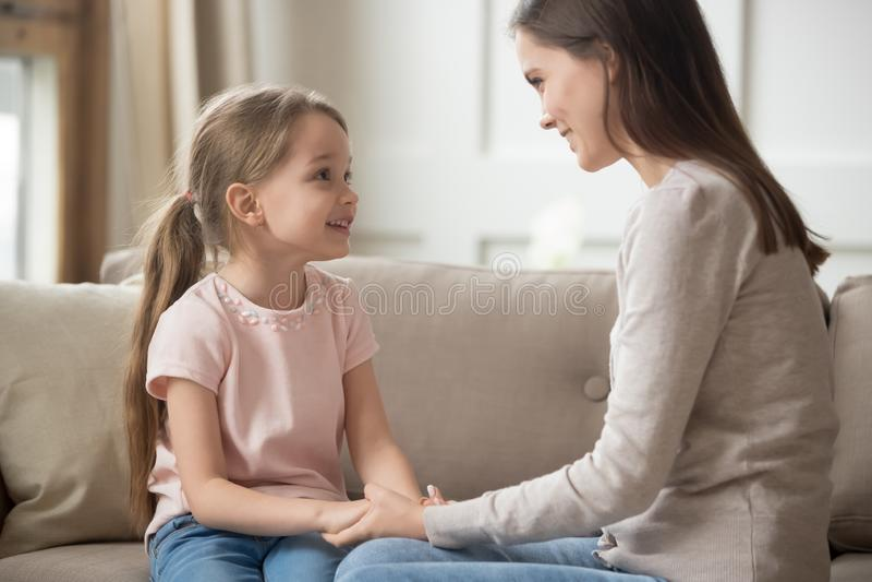 Älska modern och barnet som rymmer händer som talar sammanträde på soffan royaltyfri fotografi