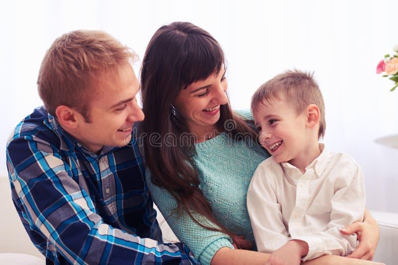 Älska modern och fadern som ser deras le barn fotografering för bildbyråer