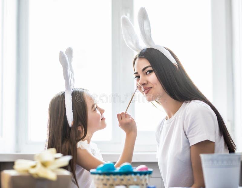 Älska modern och hennes dotter som målar easter ägg och har vit, gyckel Hemtrevlig hem- atmosfär Påsk royaltyfria bilder