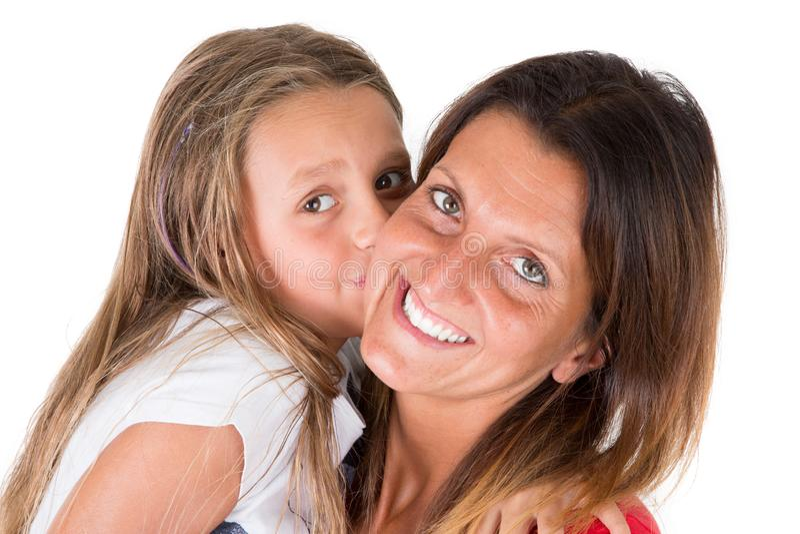 Älska modern och hennes dotterbarnflicka som kysser och kramar på vit bakgrund royaltyfria foton