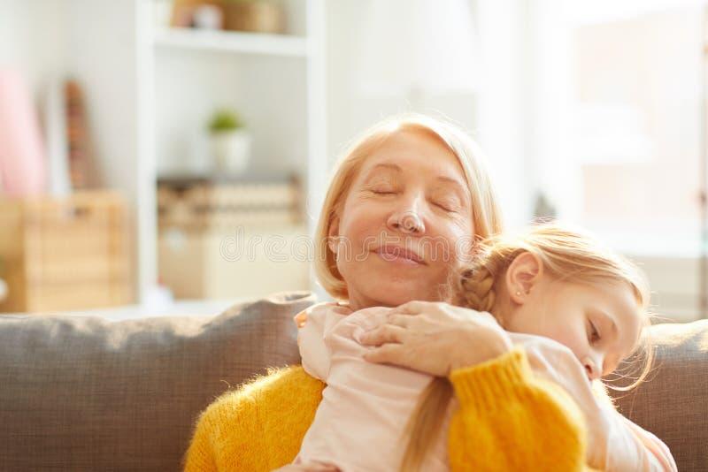 Älska modern som omfamnar dottern arkivbilder