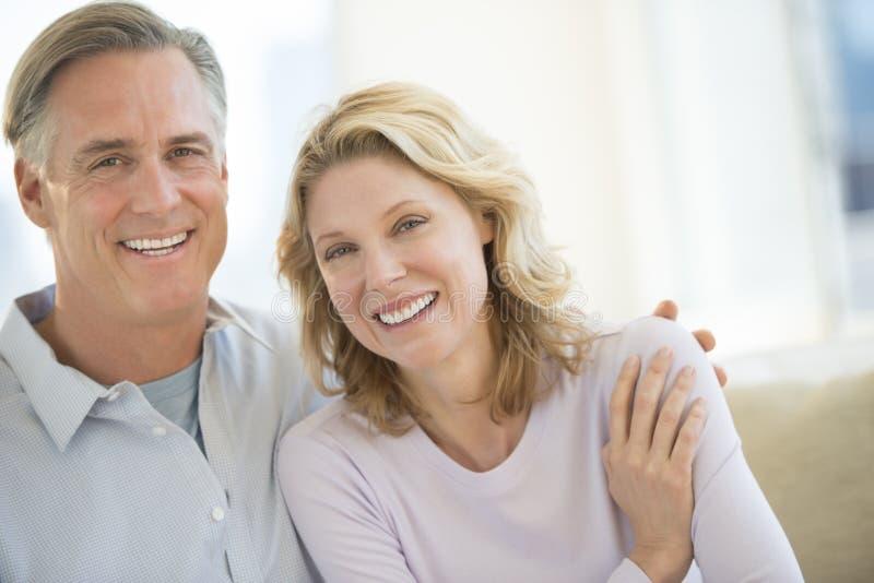 Älska mogna par som hemma ler arkivfoton