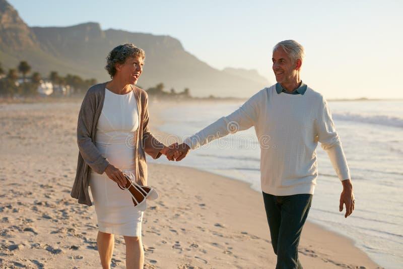 Älska mogna par som strosar på stranden fotografering för bildbyråer