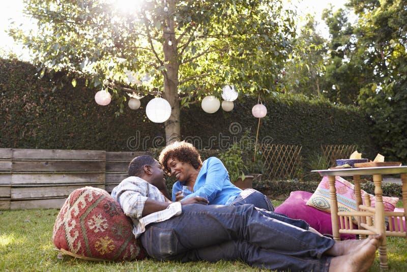 Älska mogna par som tillsammans tycker om drinkar i trädgård fotografering för bildbyråer