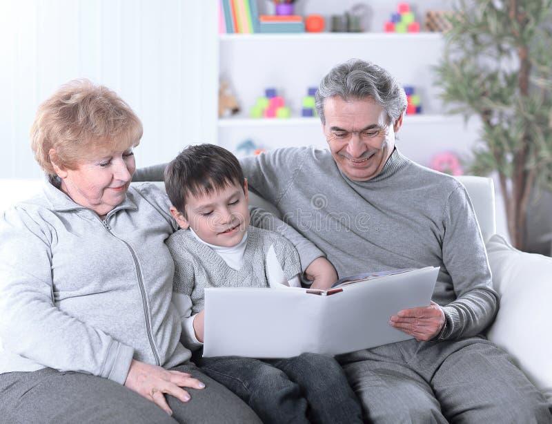 Älska morföräldrar med barnbarnsammanträde på soffan arkivbild