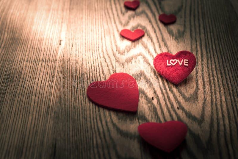 ÄLSKA ordet på röd hjärta på trätabellbakgrunderna med kopieringsutrymme royaltyfri bild