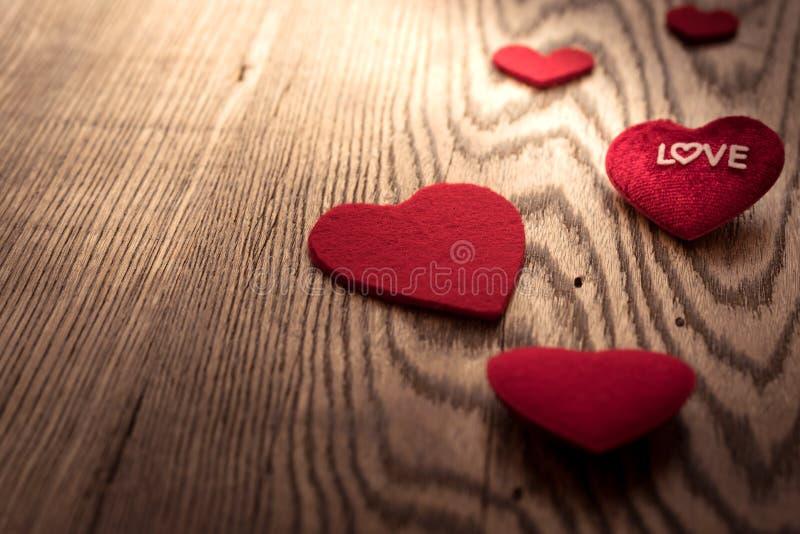 ÄLSKA ordet på röd hjärta på trätabellbakgrunderna med kopieringsutrymme arkivbild
