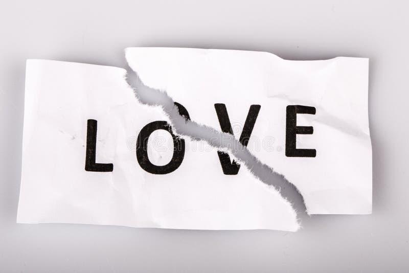 älska ordet på sönderrivet papper - brutet förälskelsebegrepp arkivfoto