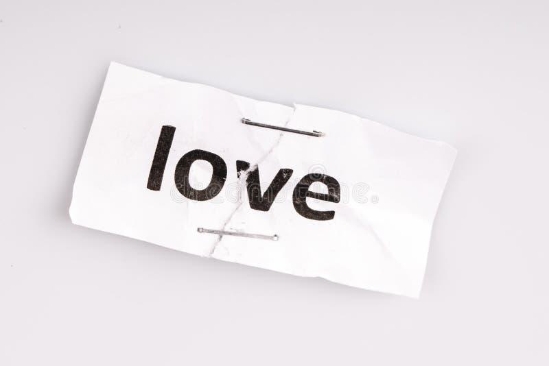 Älska ordet som är skriftligt på sönderrivet och häftat papper royaltyfri bild