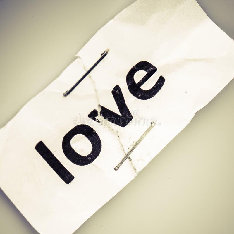 Älska ordet som är skriftligt på sönderrivet och häftat papper royaltyfri foto
