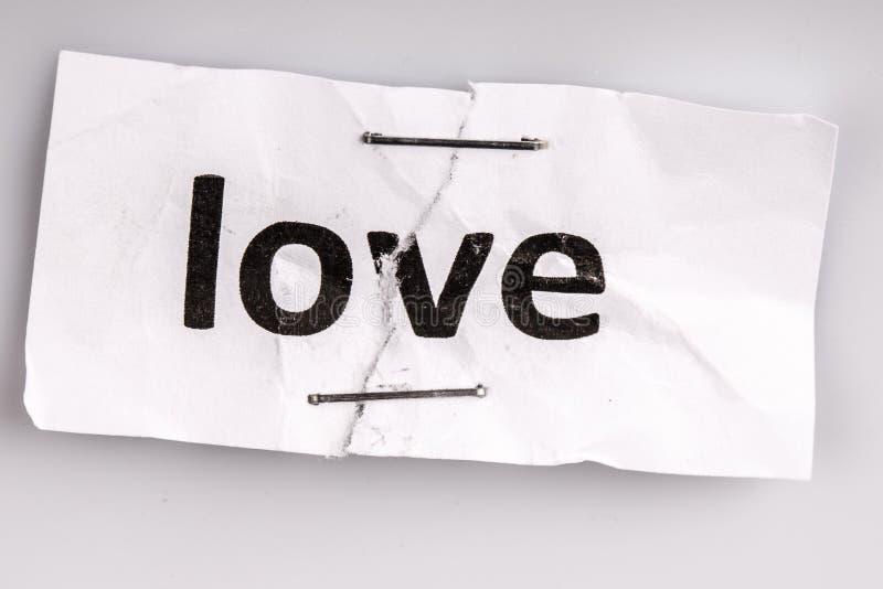 Älska ordet som är skriftligt på sönderrivet och häftat papper royaltyfria bilder