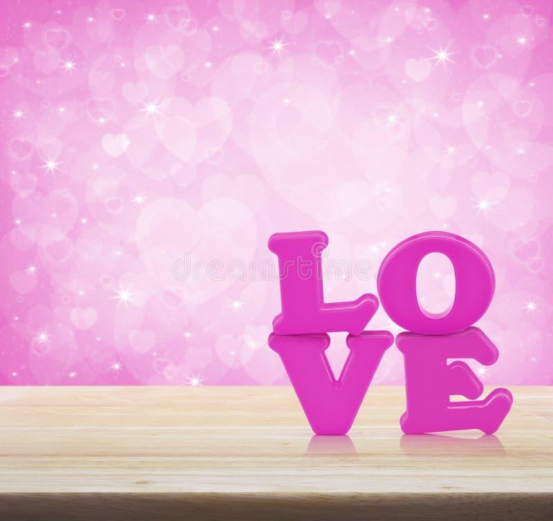 Älska ordleksaken på trätabellen över ljus - rosa hjärtabokehbackgr royaltyfri foto